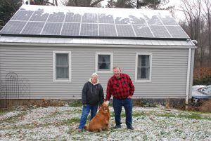 Carol and Bill in front of their solar home