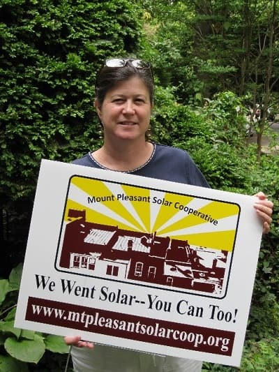 Anya Schoolman displays a Mt. Pleasant Solar Cooperative sign in 2007.