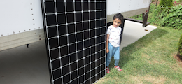 Child stands next to solar panel