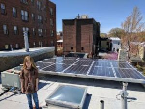 A young co-op member with her family's rooftop PV system