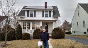 Dave Pruett stands outside of his newly solarized home.