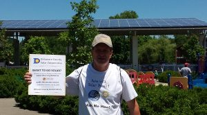 David Carpenter holding a flyer for an OH SUN information session