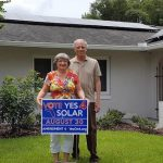 Two Florida solar home owners stand in front of a yard sign supporting a solar power friendly ballot initiative