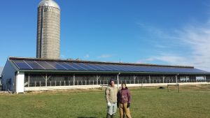 two people in the foreground, a lawn, a barn with solar panels, and a silo