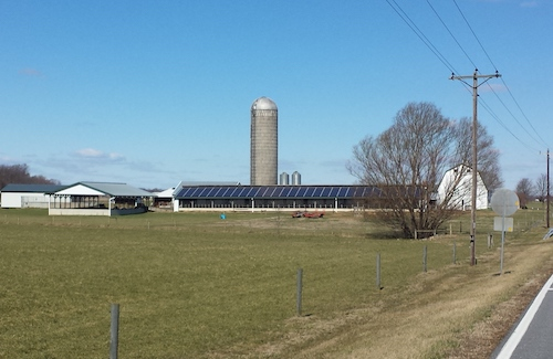 A farm with grassy area in the foreground and building in the background, one with solar panels