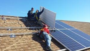 Solar installers on an asphalt shingle roof