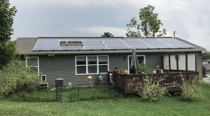 Solar panels on a green ranch style home with a grey roof