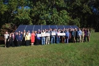 Participants pose in front of solar panels at the 2016 Maryland Solar Congress