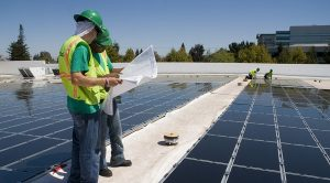 Installers work on a rooftop solar system in Oklahoma