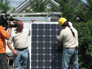 A worker demonstrates solar installation while a camera crew looks on