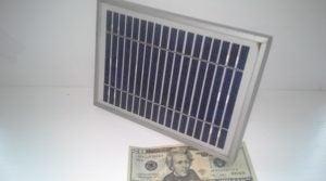 A solar panel over a twenty dollar bill