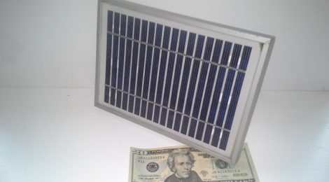 A solar panel over a twenty dollar bill