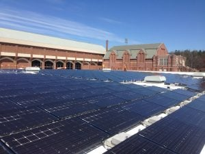 Two brick buildings and rows of solar panels