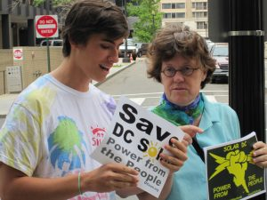 "A young man and an older woman protest in support of solar in DC. Their signs say, ""Save DC Solar Power from the People."""