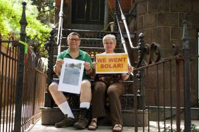 two people in front of their home holding a We Went Solar sign