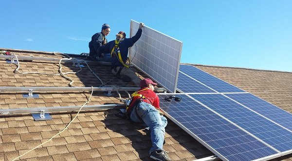 Installers mounting solar panels on a multi-array system