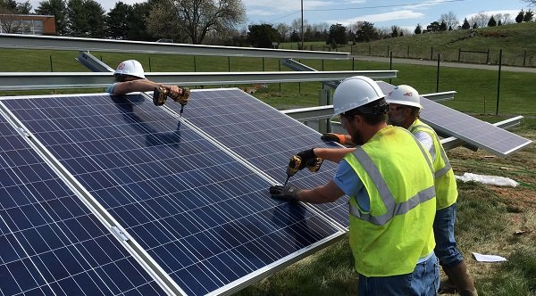 Installers work on a community solar project in Virginia.