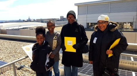 Shiela Credel (middle) and other recipients of electricity bill credits from the first community solar project in D.C. enjoyed seeing some of the panels that make up the solar system.