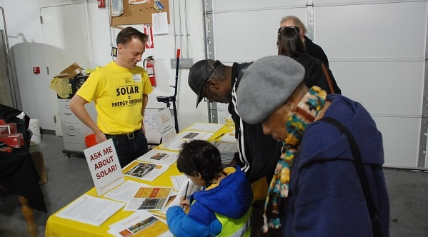Corey at the Ask Me About Solar table 600x332-min