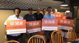 """A group of solar supporters holds signs that read """"Go Solar"""" in Canbria County."""