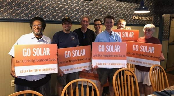 "A group of solar supporters holds signs that read ""Go Solar"" in Canbria County."