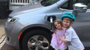 The Bruno family children pose with their new electric vehicle and Level 2 charger.