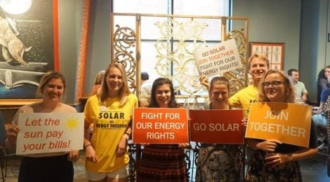 Solar supporters hold signs reading Go Solar, Join Together, and Fight for our Energy rights!