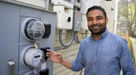 A solar homeowner in Millvale, Pennsylvania shows off his energy meter and his solar inverter.