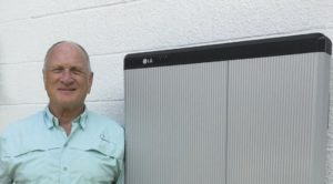 A solar homeowner stands next to his battery storage unit in his home.