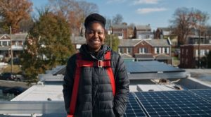 LaToya Smith, a Solar for All recipient in Ward 7, stands in front of her new solar system during the installation.