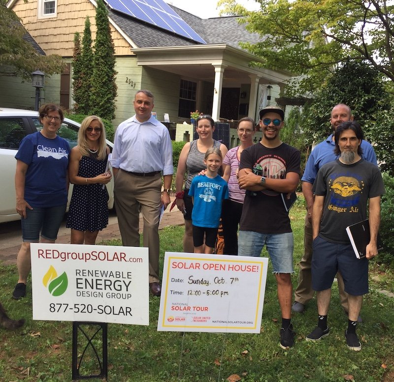 Family in front of their house, a solar panel in the garden