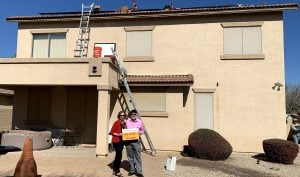 Homeowners pose with their soon to be installed solar array.
