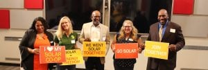 Group of DC residents holding signs about going solar