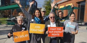 Several people with hands up, others holding solar signs