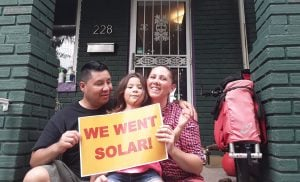 """Pergola family holding """"we went solar"""" sign on front porch"""