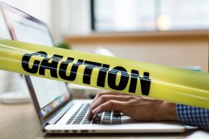 caution tape over person using the internet