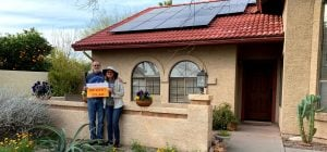 A couple in front of their house which has solar panels on the roof