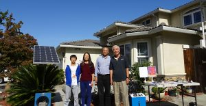 A family in front of a house with a solar panel in the garden