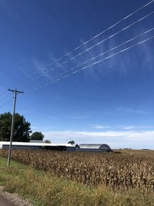 shows electric lines and pole beside corn field, barns, and solar panels