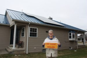 """Woman holding a sign that says """"we went solar"""" in front of her home and solar installation"""