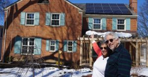 happy solar homeowners in front of their roof