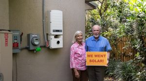 """Solar home owners next to utiltiy meter with a sign that says """"We Went Solar"""""""